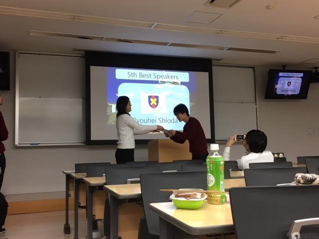 七海さんから塩田くんへ賞状が渡されるのを写真に収める(KDS広報)のかえるさん図